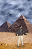 Indiana Jones Style Action Hero and Adventure. An Indiana Jones action hero character style shows our adventurer in the desert by the Great Pyramids of Egypt in royalty free stock photo