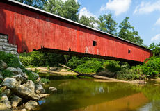 Indiana Red Covered Bridge. The Oakalla Covered Bridge crosses Big Walnut Creek in Putnam County, Indiana. The covered bridge with bright red weathered siding Stock Photo