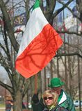 People walking with Irish Flag at St Patrick's Day Stock Image