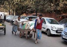 Indiani lavoranti duri che spingono onere gravoso tramite le vie di Delhi Fotografia Stock
