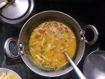 Indianin gotujący jarski curry w kuchennych naczyniach obraz stock