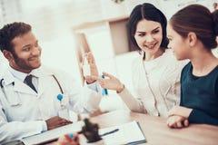 Indianin lekarka widzii pacjentów w biurze Lekarka daje matki i córki nosowa kiść zdjęcie stock