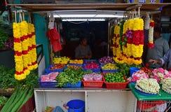 Indianina stoiskowego sprzedawania kwiatu różni pączki na stołowym koszu, zielonym wapnie, liściach i colourful girlandy niedalek Zdjęcie Royalty Free