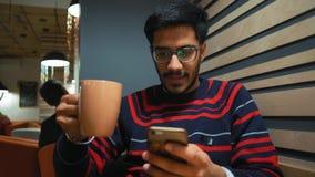 Indiano Guy Communicates con Smartphone e caffè delle bevande in un caffè archivi video