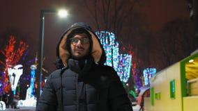 Indiano Guy Walking nel parco di festa di notte di inverno stock footage