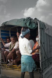 Indians riding in truck, guy standing on rear bumper. India, Karnataka - January 17, 2016: Indian transport. Colorful picture of Indians riding in truck, guy Stock Images