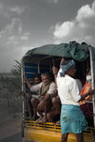 Indians riding in truck, guy standing on rear bumper. India, Karnataka - January 17, 2016: Indian transport. Colorful picture of Indians riding in truck, guy Stock Photos