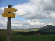 Indicações das montanhas no primeiro plano com algumas setas de madeira amarelas com afinal as montanhas do Auvergne em França Foto de Stock