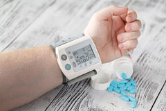 Indicación de la tensión arterial alta de Tonometer en el male& x27; brazo de s píldoras médicas de la hipertensión en el fondo Fotografía de archivo libre de regalías