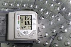 Indicación y píldoras de la tensión arterial alta de Tonometer en ampollas de la hoja Imágenes de archivo libres de regalías