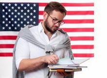 Indicador americano Hombre joven sonriente en fondo de la bandera de Estados Unidos foto de archivo libre de regalías