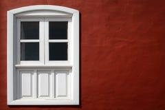 Indicador branco e brilhante em uma parede vermelha. Imagem de Stock