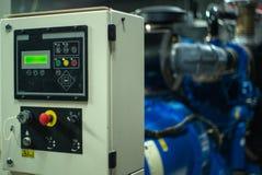 Indicador da iluminação do close up no armário de controle na sala elétrica com o gerador elétrico borrado no fundo imagem de stock