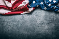 Indicador de los E Indicador americano Bandera americana que miente libremente en fondo concreto Tiro del estudio del primer Foto Imagen de archivo