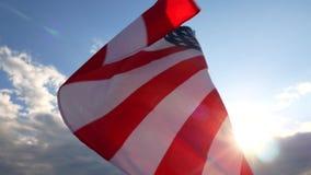 Indicador de los Estados Unidos de América El el blanco rojo y azul U S, A, protagoniza las rayas, volando con el cielo azul almacen de metraje de vídeo