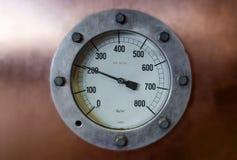 Indicador de presión del vintage en fondo borroso con señalar de la flecha Imagen de archivo libre de regalías