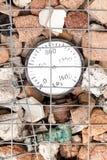 Indicador de presión viejo embalado en una roca Gabion Fotos de archivo libres de regalías