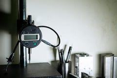 Indicador del calibrador de micrómetro en el soporte de medición en el departamento de la garantía de calidad Foto de archivo