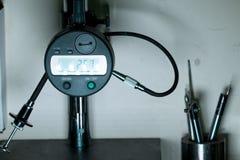 Indicador del calibrador de micrómetro en el soporte de medición en el departamento de la garantía de calidad Imagen de archivo