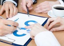 Indicando alle mani del grafico di discussione dei responsabili Immagine Stock