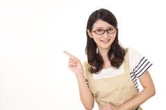 Indicare asiatico sorridente della casalinga Immagini Stock