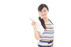 Indicare asiatico sorridente della casalinga Fotografia Stock