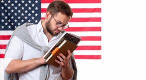 Indicateur américain Jeune homme de sourire sur le fond de drapeau des Etats-Unis Photos libres de droits