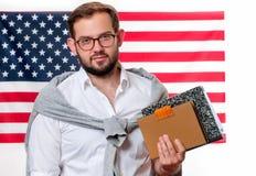 Indicateur américain Jeune homme de sourire sur le fond de drapeau des Etats-Unis Images stock
