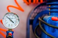 Indicateur de pression avec le fil orange et la pompe bleue Photo libre de droits