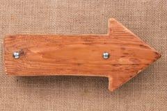 Indicateur fait de bois léger avec des rivets en métal sur la toile de jute D'isolement sur le fond blanc Image libre de droits