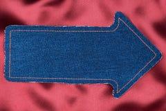 Indicateur fait en tissu de denim avec piquer jaune sur la soie rouge Images stock