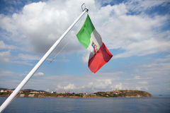 Indicateur italien ondulant au-dessus de la mer Photo stock