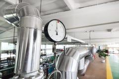 Indicateurs de pression mécaniques ronds sur des canalisations Photos stock