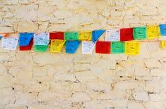 Indicateurs tibétains bouddhistes de prière contre le mur Photographie stock libre de droits