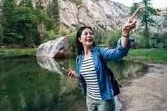 Indication excitée par femme gaie de randonneur le ciel photographie stock
