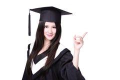 Indication par les doigts d'étudiant de graduation pour copier l'espace Photographie stock libre de droits