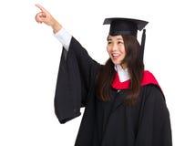 Indication par les doigts de fille d'étudiant de graduation  Photographie stock libre de droits