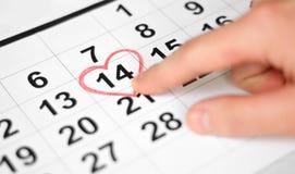 Indication par les doigts de main au 14 février Feuille de calendrier avec la date du 14 février marquée par forme rouge de coeur image stock