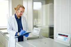 Indications. Clinician rewriting indications from display on plasma centrifuge royalty free stock image