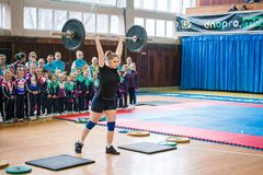 Indicative performance of weightlifters at the championship in cheerleading,young girl lifts a heavy barbell, barbell weight - 60 stock photo