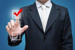 Indicatore della lista di controllo del segno di spunta di tocco dell'uomo d'affari isolato su fondo blu Fotografia Stock Libera da Diritti