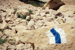 Indicatore della traccia di escursione dipinto su una pietra nell'area rocciosa del deserto Immagini Stock