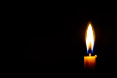 Indicatore luminoso della candela nello scuro fotografia stock