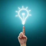 Indicatore luminoso di lampadina di Drawning sulla punta delle dita delle donne Fotografia Stock Libera da Diritti