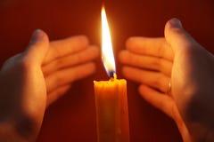 Indicatore luminoso e mani della candela Fotografia Stock