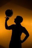 Indicatore luminoso posteriore - siluetta del globo della holding dell'uomo Immagine Stock
