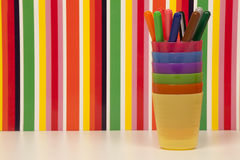 Indicatori colorati, tazze di plastica impilate e fondo multicolore delle bande Immagini Stock Libere da Diritti