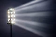Indicatori luminosi dello stadio contro cielo notturno scuro Immagine Stock
