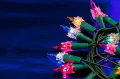 Indicatori luminosi di Cristmas su un azzurro Fotografia Stock Libera da Diritti