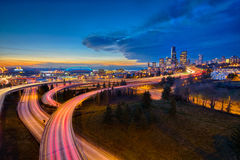 Indicatori luminosi di trascinamento dell'automobile e l'orizzonte di Seattle al tramonto Fotografia Stock